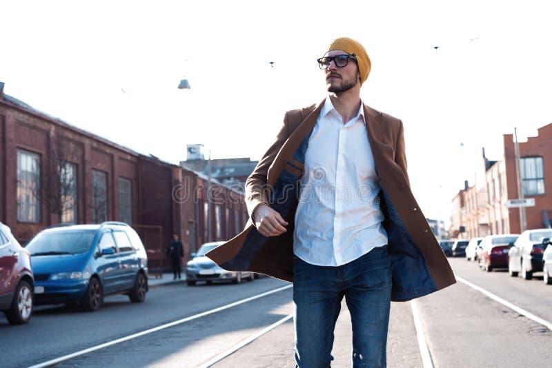 Adatti il ritratto dell'uomo Giovane in vetri che portano cappotto che cammina giù la via immagine stock libera da diritti
