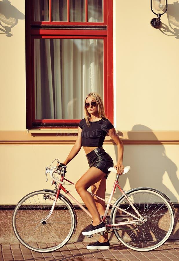 Adatti il ritratto della donna bionda attraente con un bicyc d'annata fotografia stock libera da diritti