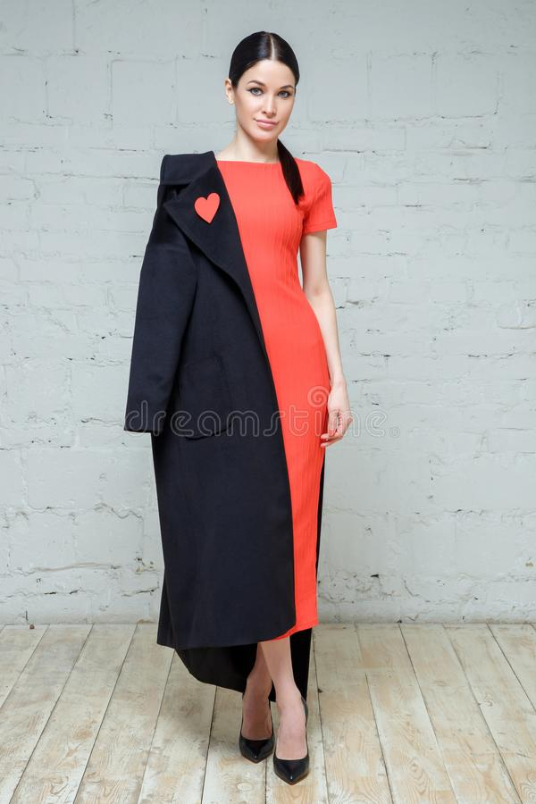 Adatti il ritratto della donna elegante in cappotto nero e nel vestito rosso immagini stock