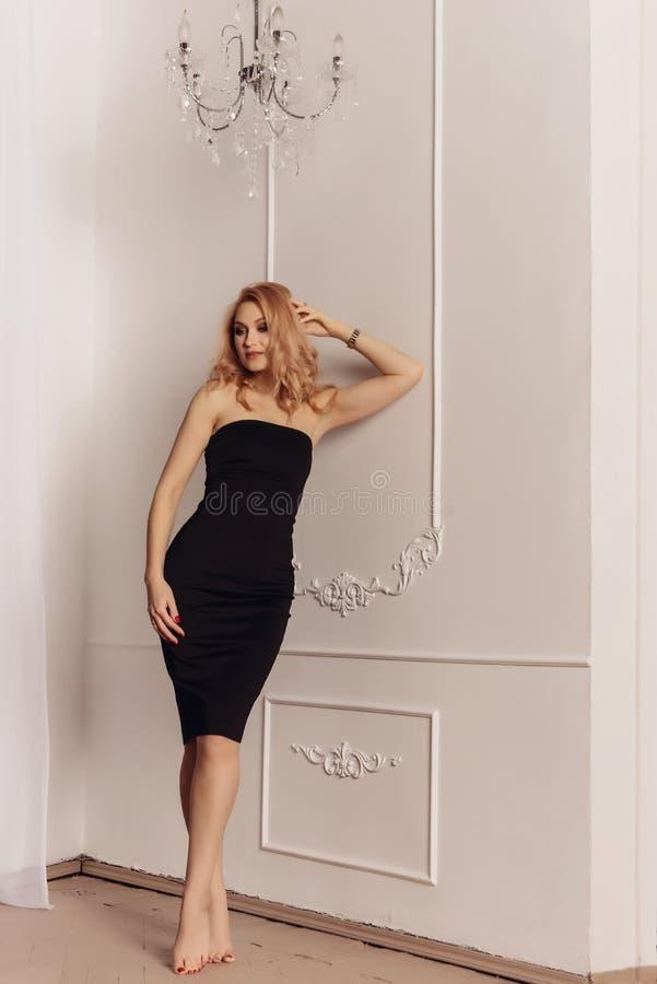 Adatti il ritratto della donna sexy di estate calda del vestito nero vicino a fondo bianco fotografia stock libera da diritti