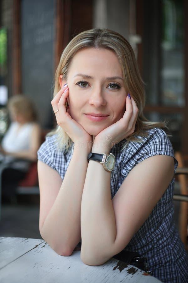 Adatti il ritratto della giovane donna che si siede in un caffè della via fotografie stock libere da diritti
