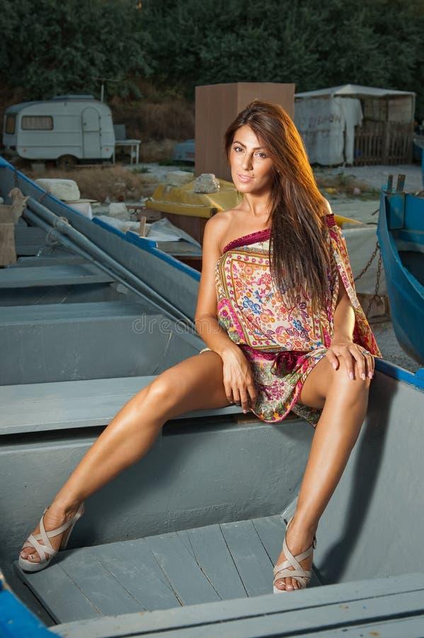 Adatti il ritratto della ragazza castana sexy in costume da bagno che si appoggia una barca di legno Donna attraente sensuale con fotografia stock libera da diritti