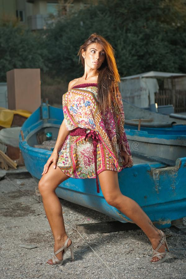Adatti il ritratto della ragazza castana sexy in costume da bagno che si appoggia una barca di legno Donna attraente sensuale con immagine stock libera da diritti