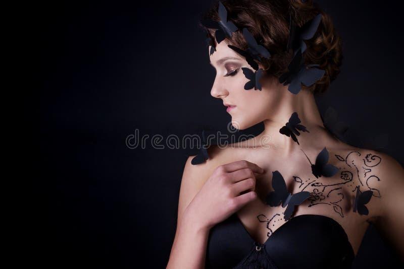 Adatti il ritratto di bella ragazza nel profilo su un fondo nero con le farfalle nere sul corpo immagini stock
