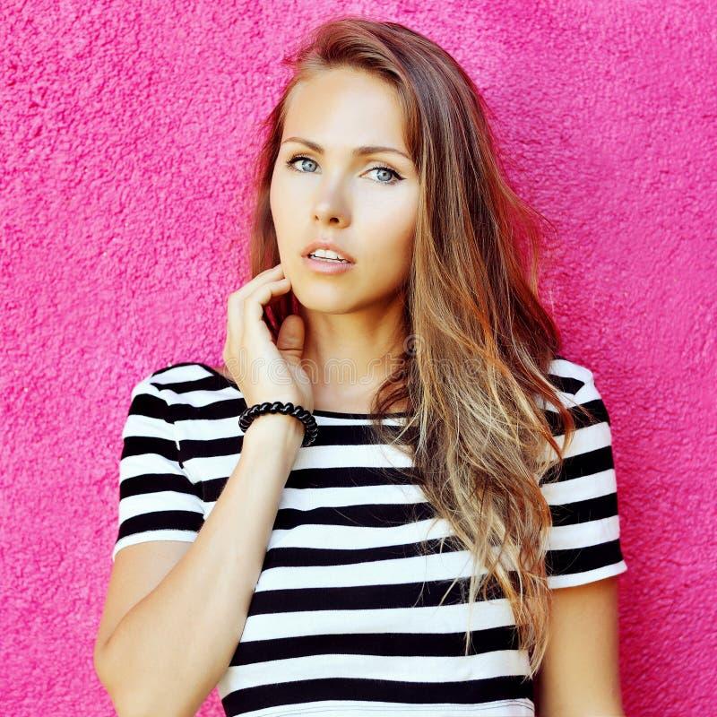 Adatti il ritratto di bella ragazza vicino alla parete rosa fotografie stock