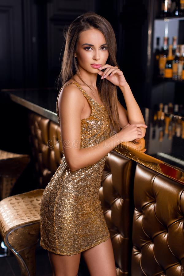 Adatti il ritratto di bello castana in vestito brillante dorato con trucco luminoso fotografia stock libera da diritti