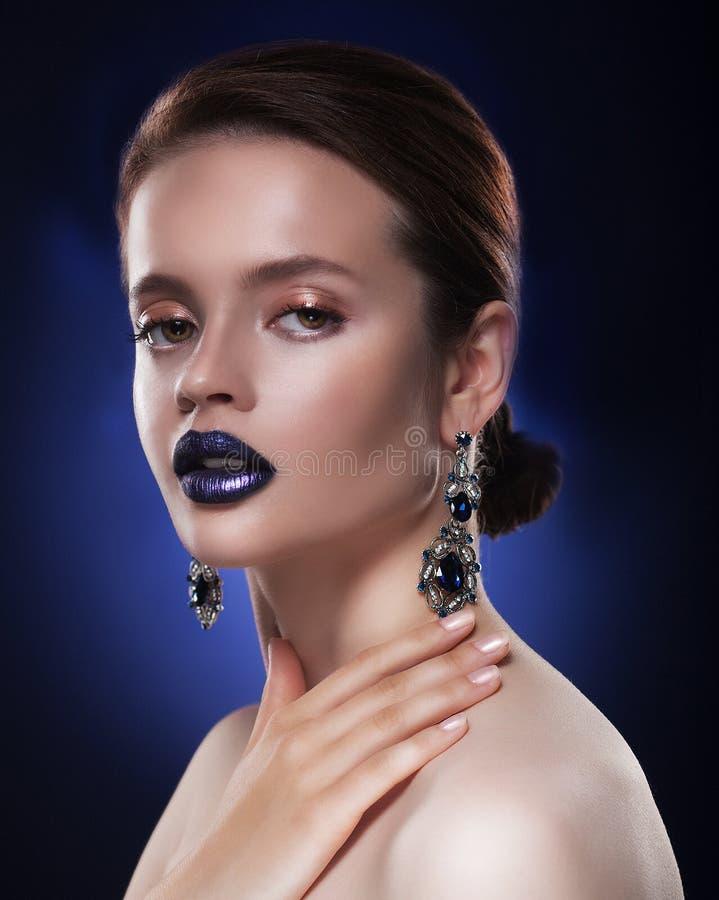 Adatti il ritratto di giovane bella donna con gioielli Trucco perfetto Orli blu fotografia stock