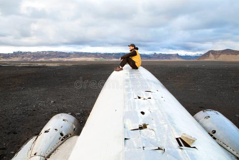 Adatti il tipo che si siede su un aereo che è caduto sulla spiaggia nera o fotografia stock