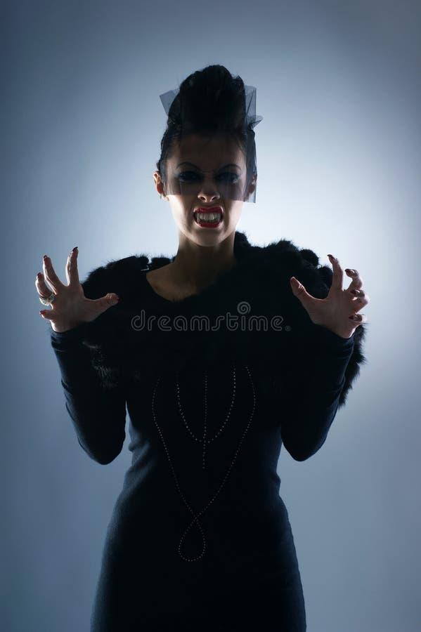 Adatti il tiro di un vampiro femminile in un vestito scuro fotografia stock libera da diritti