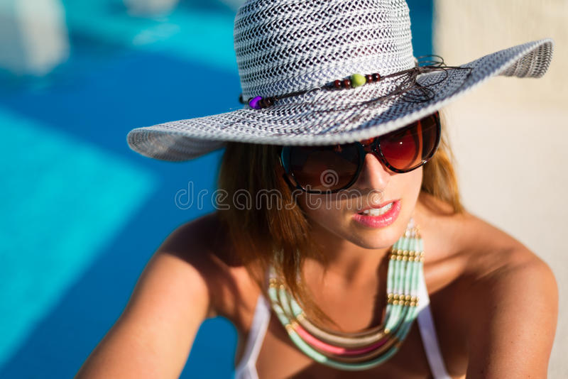 Adatti la bella donna che si rilassa al poolside sulle vacanze estive immagine stock libera da diritti