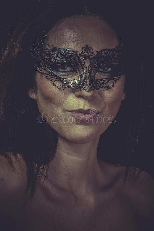 Adatti la donna castana in arricciamenti neri del metallo della maschera fotografia stock libera da diritti