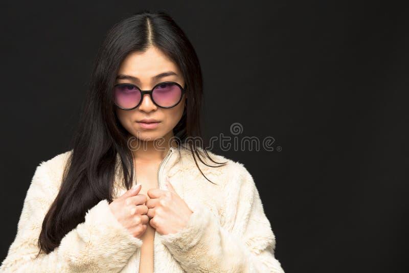 Adatti la donna di modello asiatica in occhiali da sole in studio fotografia stock