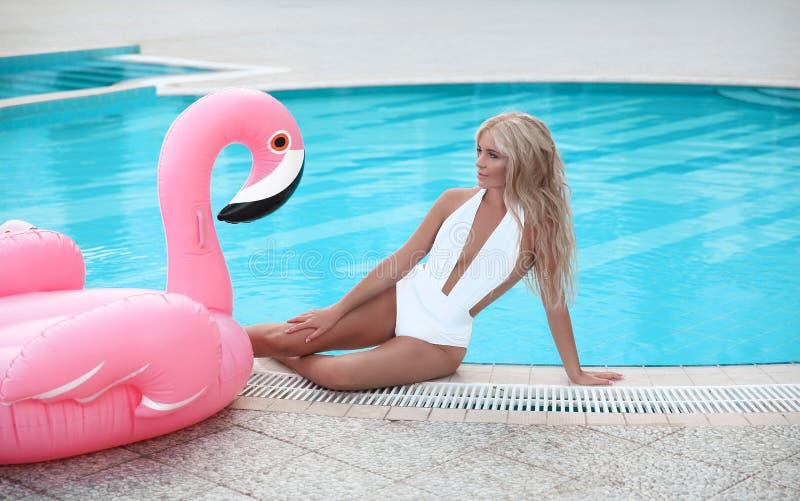 Adatti la donna di modello bionda sexy in bikini bianco che posa sul rosa dentro fotografia stock