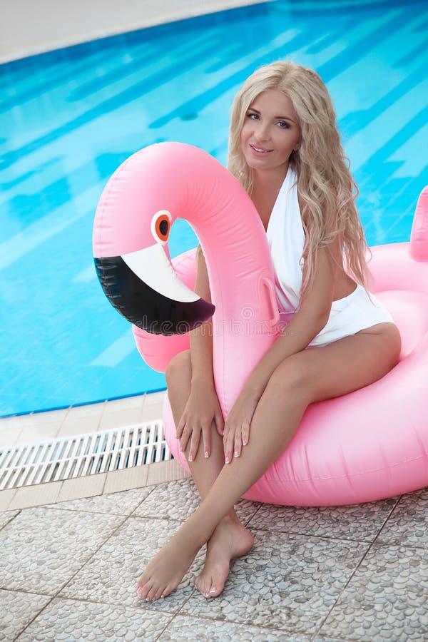 Adatti la donna di modello bionda sexy in bikini bianco che posa sul rosa dentro fotografie stock libere da diritti