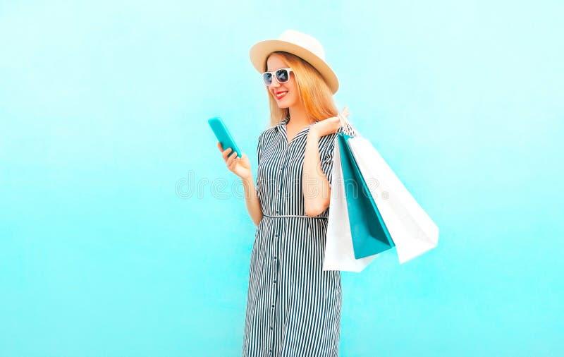 Adatti la donna sorridente felice con lo smartphone, sacchetti della spesa immagini stock libere da diritti