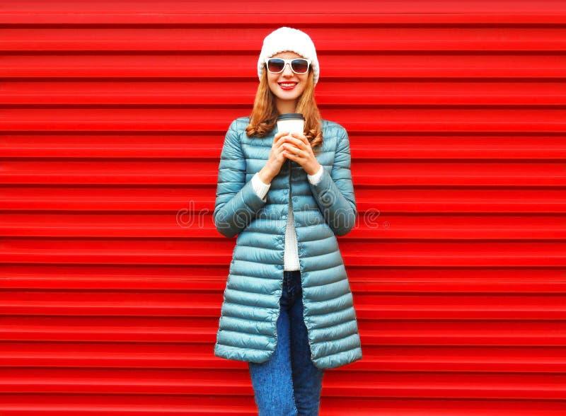 Adatti la donna sorridente felice con la tazza di caffè su fondo rosso fotografia stock