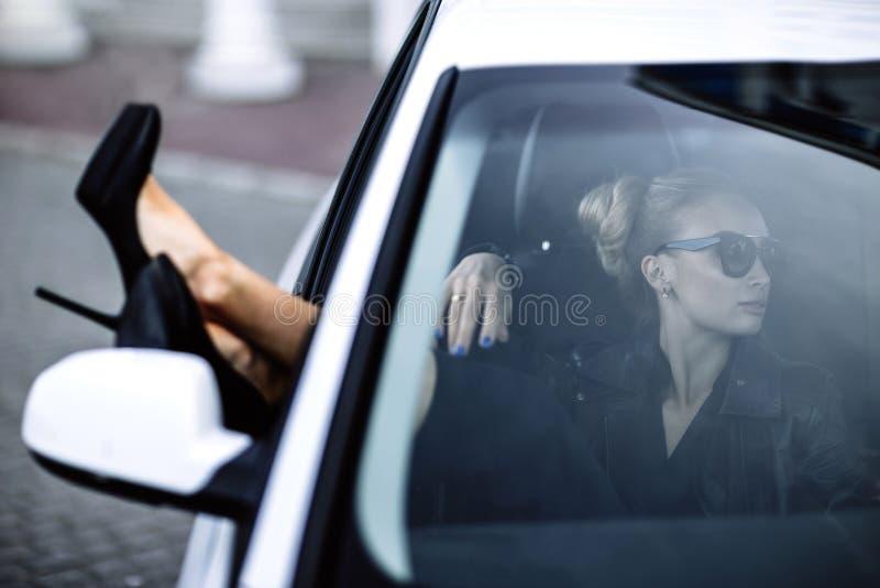 Adatti la foto all'aperto di bella donna sexy con capelli scuri in bomber nero ed occhiali da sole che posano in auto lussuosa fotografia stock