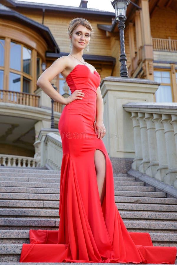Adatti la foto all'aperto di bella donna sexy in vestito rosso lussuoso che posa sulle scale in villa immagini stock