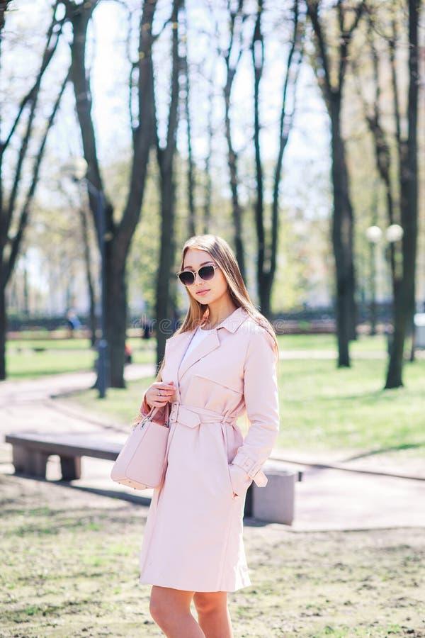 Adatti la foto all'aperto di bella giovane donna con capelli biondi in vestiti eleganti ed occhiali da sole che posano nel parco  fotografia stock