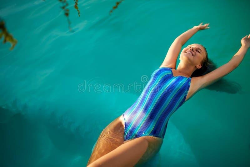 Adatti la foto della donna esile attraente con capelli biondi lunghi in costume da bagno a strisce elegante del corpo che si rila fotografia stock
