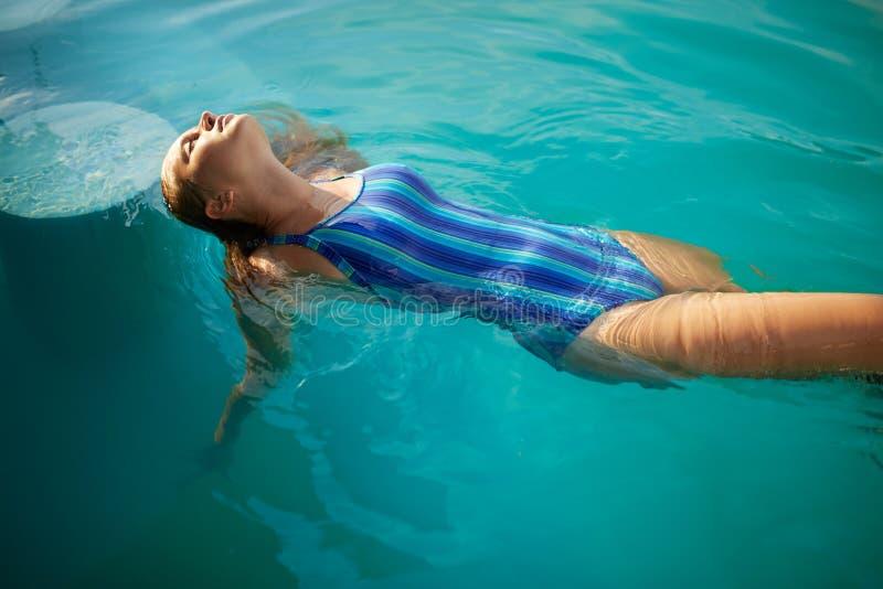 Adatti la foto della donna esile attraente con capelli biondi lunghi in costume da bagno a strisce elegante del corpo che si rila fotografie stock libere da diritti