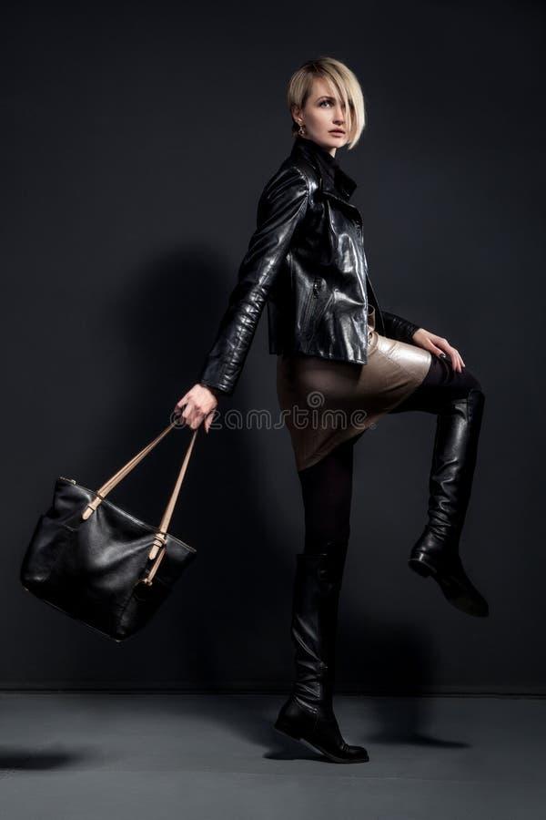 Adatti la foto della giovane donna nel jucket di cuoio, gonna di cuoio immagine stock