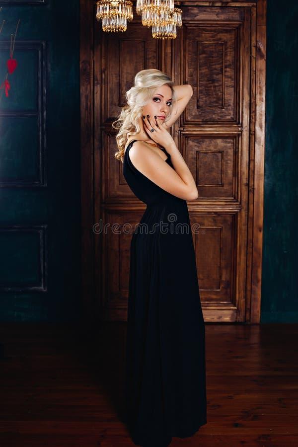 Adatti la foto di bella giovane ragazza bionda del fascino interno ricco, una donna con capelli ricci biondi nel nero elegante immagine stock