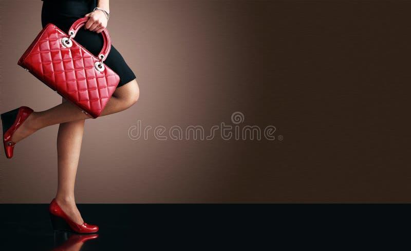 Adatti la foto, piedini sexy della donna con la borsa fotografia stock