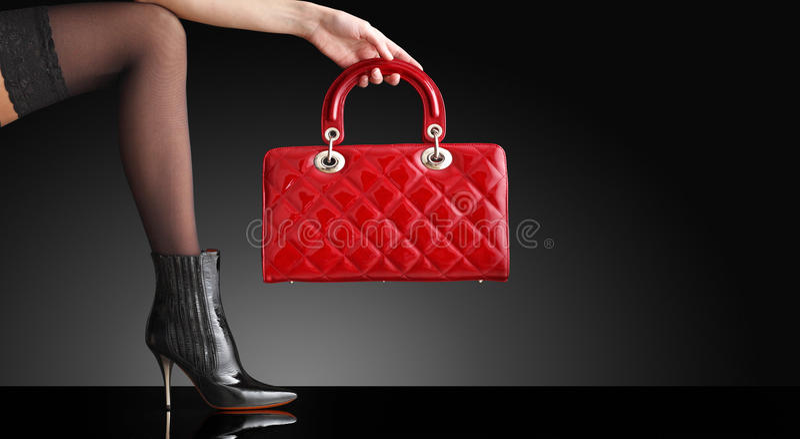 Adatti la foto, piedini sexy della donna con la borsa fotografie stock