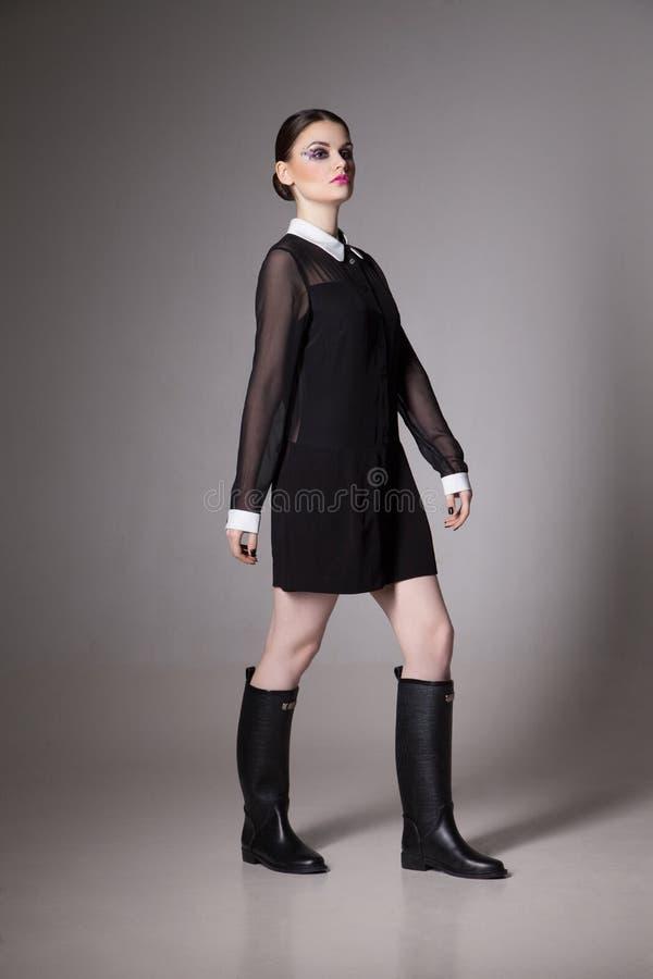Adatti la giovane donna di immagine in un vestito nero alla moda immagini stock