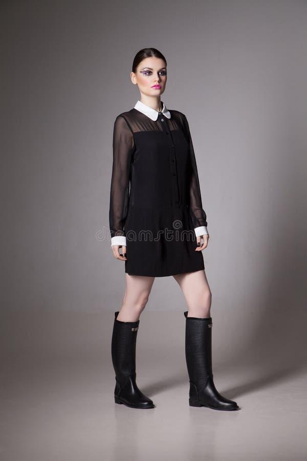 Adatti la giovane donna di immagine in un vestito nero alla moda immagine stock