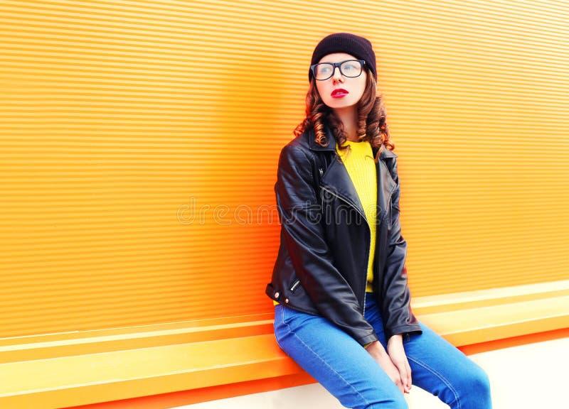 Adatti la giovane donna graziosa in rivestimento black hat della roccia sopra fondo arancio variopinto immagine stock