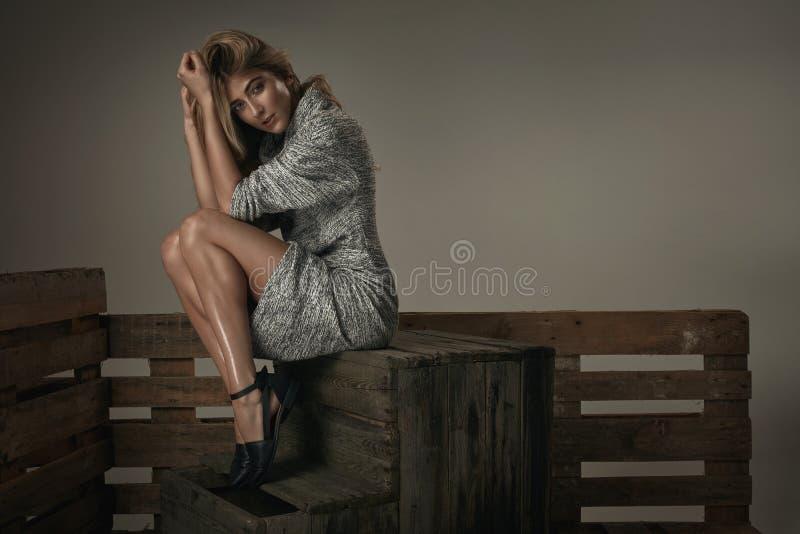 Adatti la giovane donna naturale che si siede su un petto di legno immagine stock