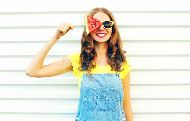 Adatti la giovane donna sorridente che tiene una fetta di anguria sotto forma di gelato fotografia stock