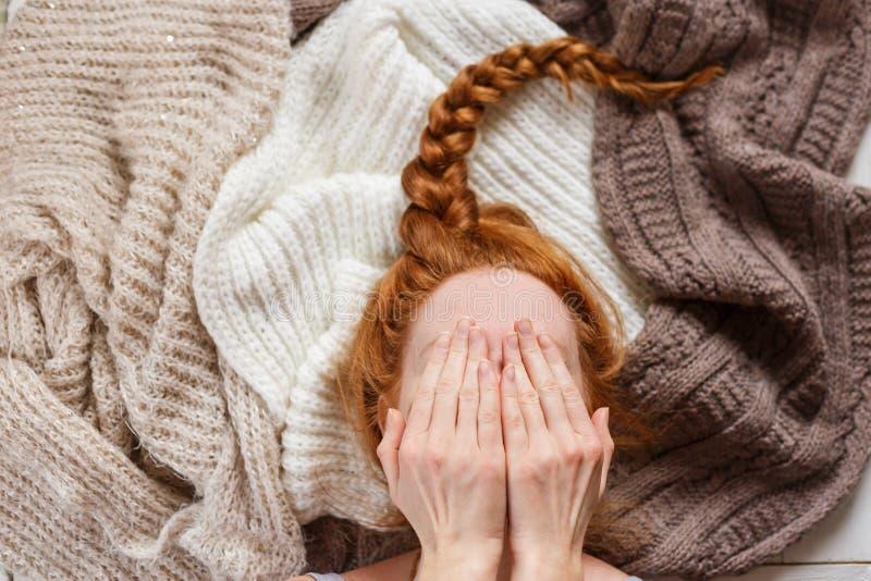 Adatti la giovane testarossa che la donna ha coperto il suo fronte a mano, trovantesi sul maglione tricottato immagine stock