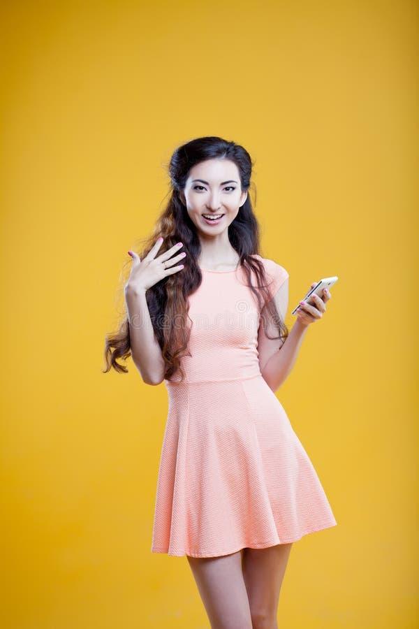 Adatti la ragazza asiatica con il telefono cellulare, nella scossa Ritratto su fondo giallo fotografia stock