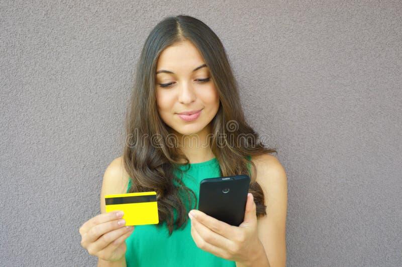 Adatti la ragazza che compra online con lo Smart Phone e la carta di credito isolati su fondo viola fotografie stock libere da diritti