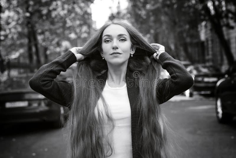 Adatti la ragazza con capelli molto lunghi contro la via della città fotografie stock
