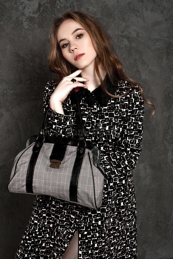 Adatti la ragazza con la borsa che posa weariing un cappotto immagine stock libera da diritti