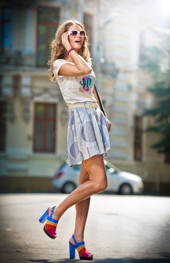 Adatti la ragazza con la minigonna, la borsa ed i tacchi alti camminante sulla via, vetri di sole fotografia stock