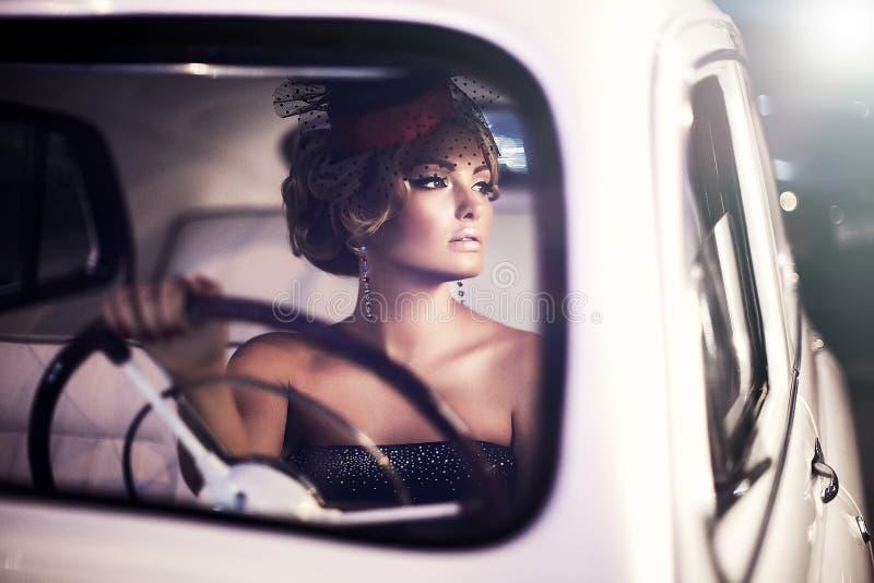 Adatti la ragazza nel retro stile che posa in vecchia automobile fotografie stock libere da diritti