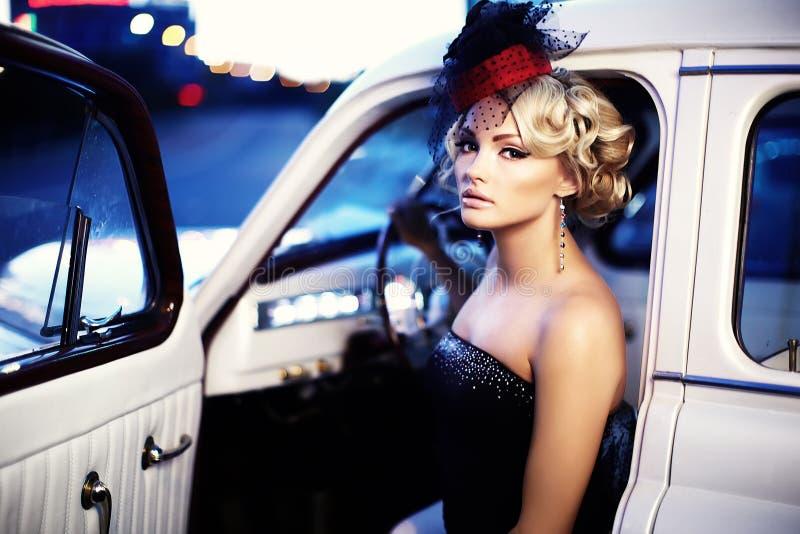 Adatti la ragazza nel retro stile che posa in vecchia automobile fotografia stock libera da diritti