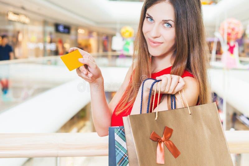 Adatti la riuscite carta di credito della tenuta della donna e borse, centro commerciale immagine stock