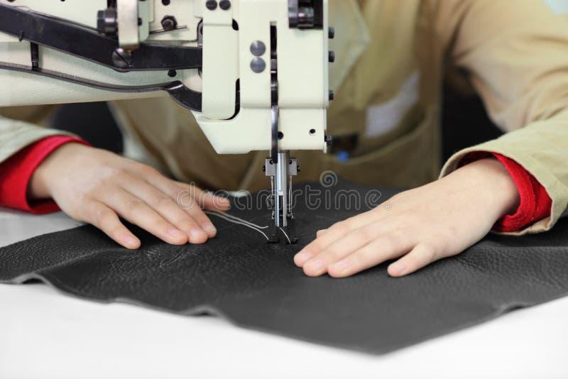 Adatti lavorare ad una macchina per cucire alla fabbrica immagini stock