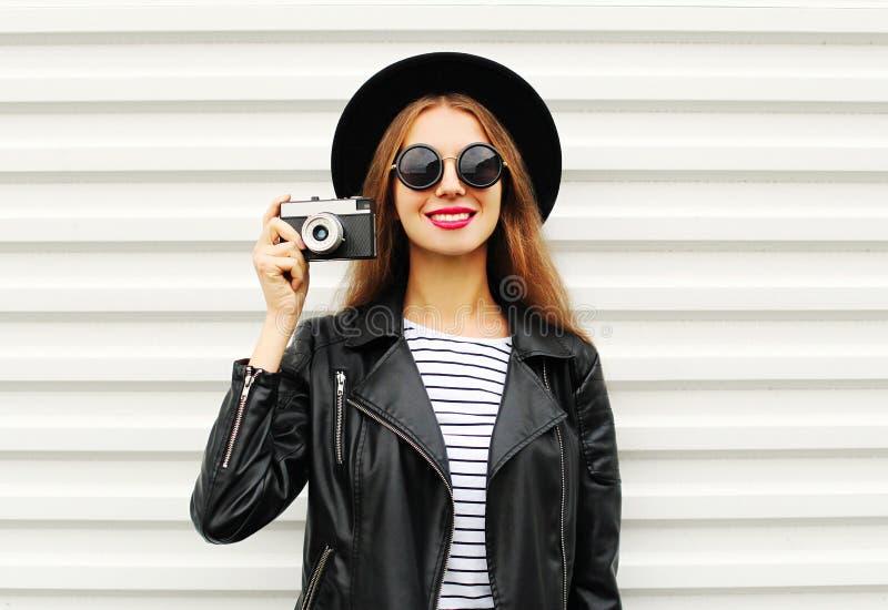 Adatti lo sguardo, modello grazioso della giovane donna con la retro macchina da presa che porta il rivestimento black hat e di c immagini stock libere da diritti