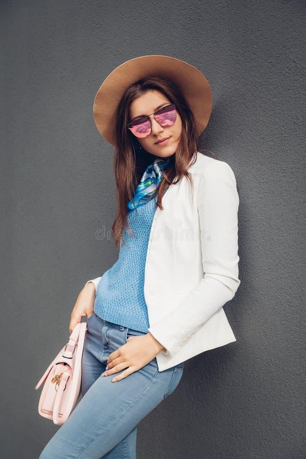 Adatti a ritratto il rivestimento d'uso della giovane donna graziosa, il cappello, occhiali da sole e borsa di tenuta sopra fondo fotografia stock