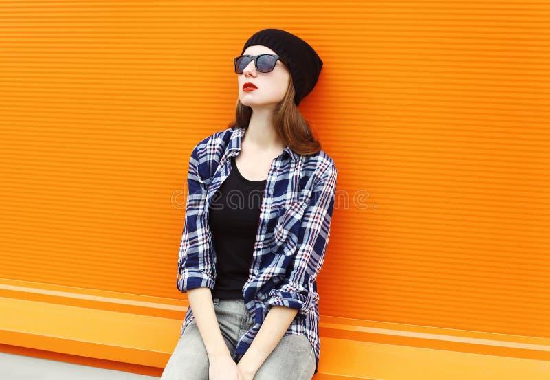 Adatti a ritratto la donna graziosa che porta un black hat, gli occhiali da sole e la camicia sopra variopinto immagine stock