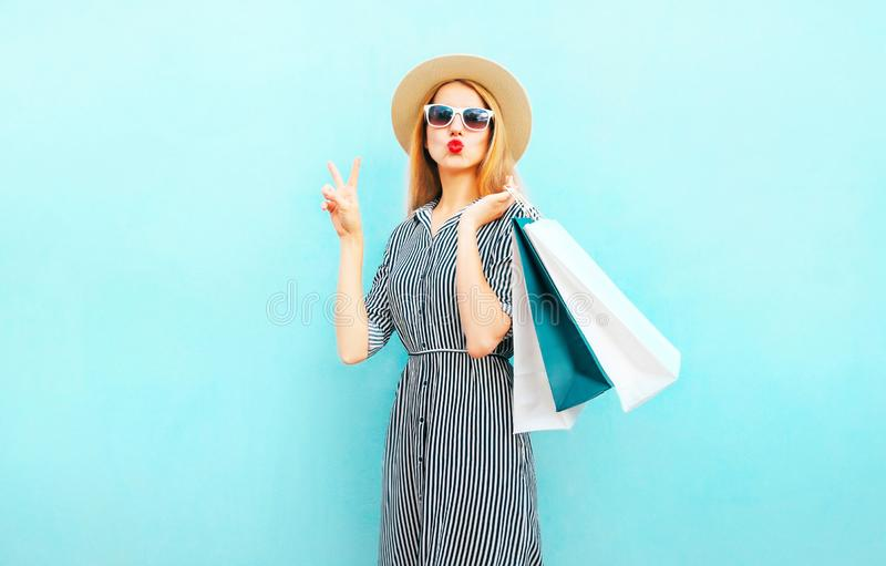 Adatti a ritratto la donna graziosa con i sacchetti della spesa in vestito a strisce immagini stock libere da diritti