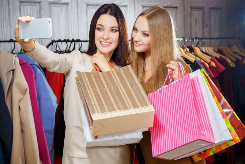 Adatti un ritratto di due giovani bei amici delle donne nel centro commerciale con molti sacchetti della spesa Fabbricazione del  fotografia stock libera da diritti