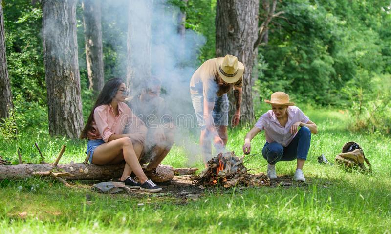 Add some wood to fire. Company friends or family making bonfire in forest nature background. Friends hang out near. Bonfire picnic. Company youth camping forest stock image